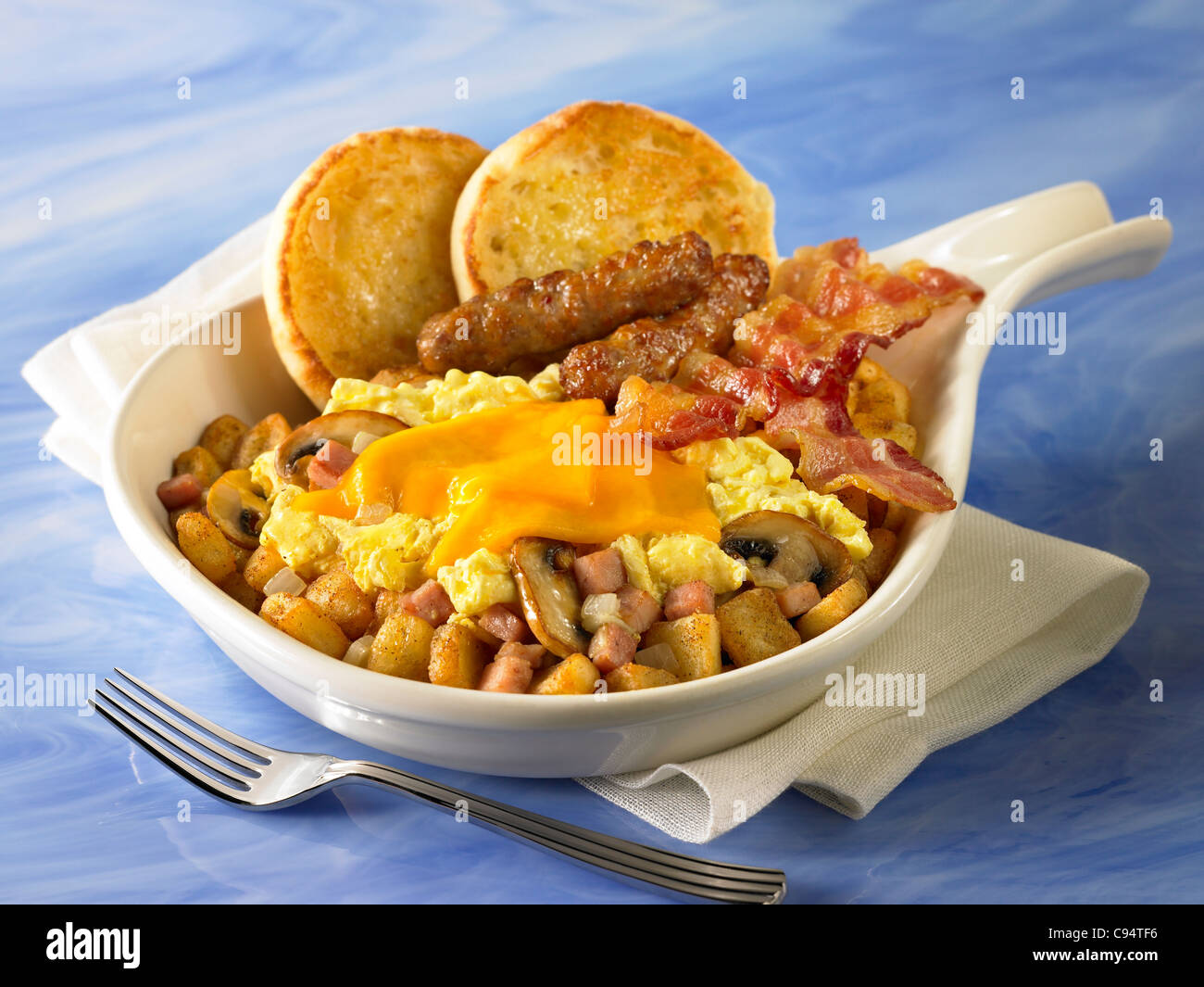 A breakfast skillet of potatoes, mushrooms and onions covered with eggs and cheese and served with bacon, sausage - Stock Image