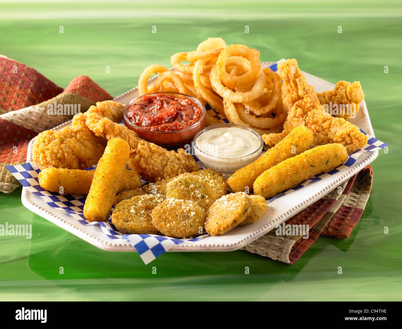 Mixed appetizer of onion rings, chicken wings, fried zucchini with sauces - Stock Image