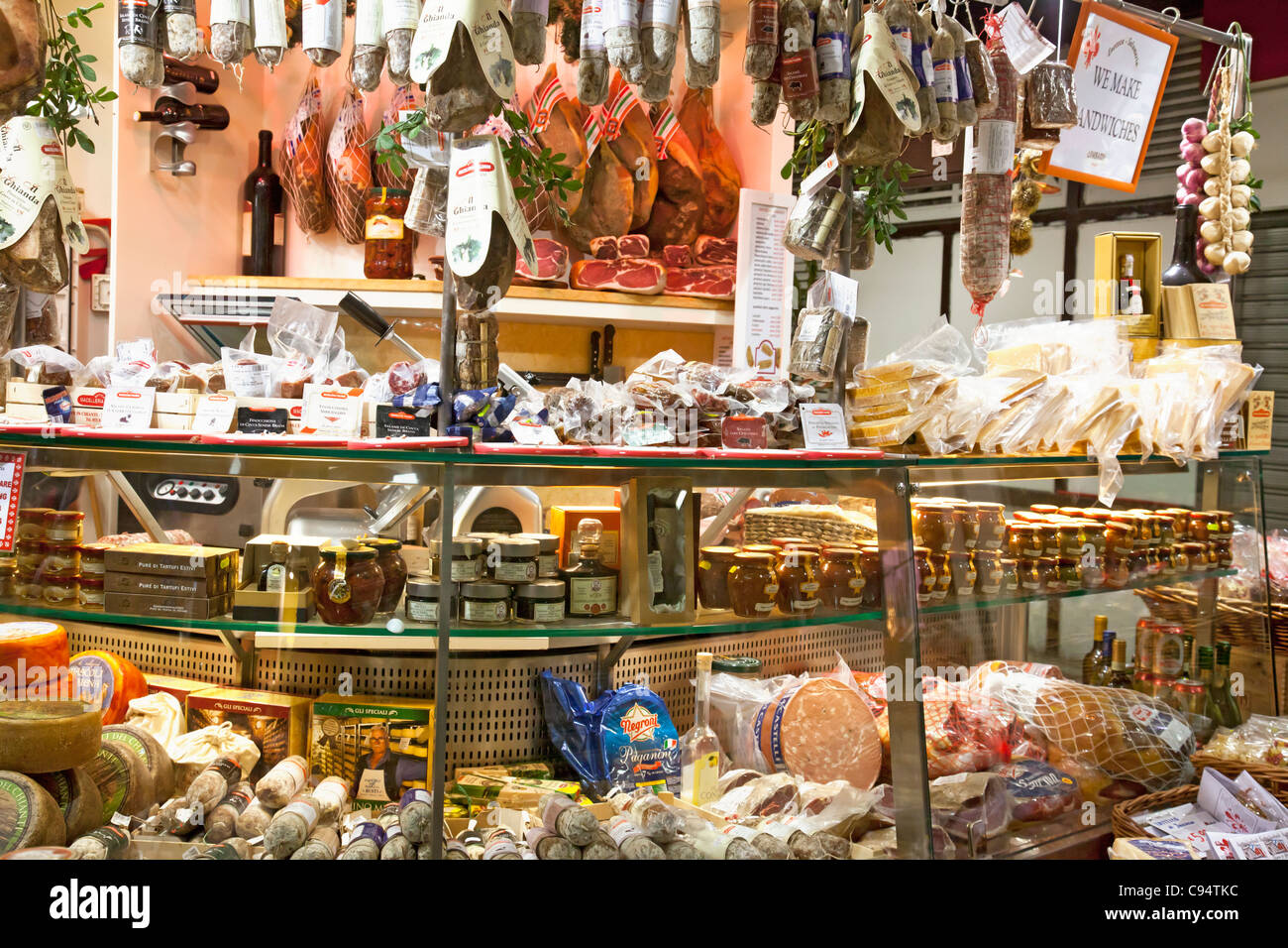 Stall selling typical Italian food at the Mercato Centrale in Florence. Proscuitto, salami, cheese, balsamic vinegar, - Stock Image