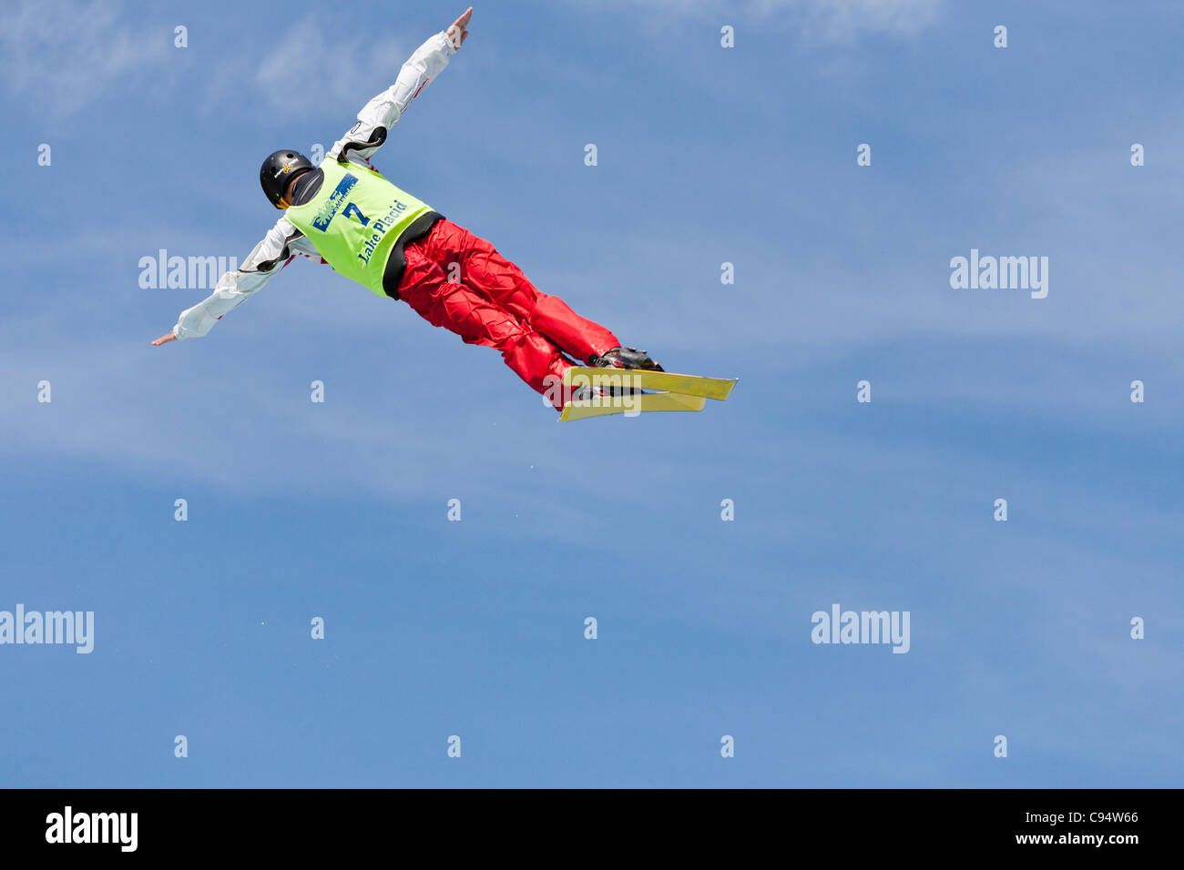 In the clouds. Ski practice.. A freestyle skier rotates through a bright blue summer sky during practice for olympic - Stock Image