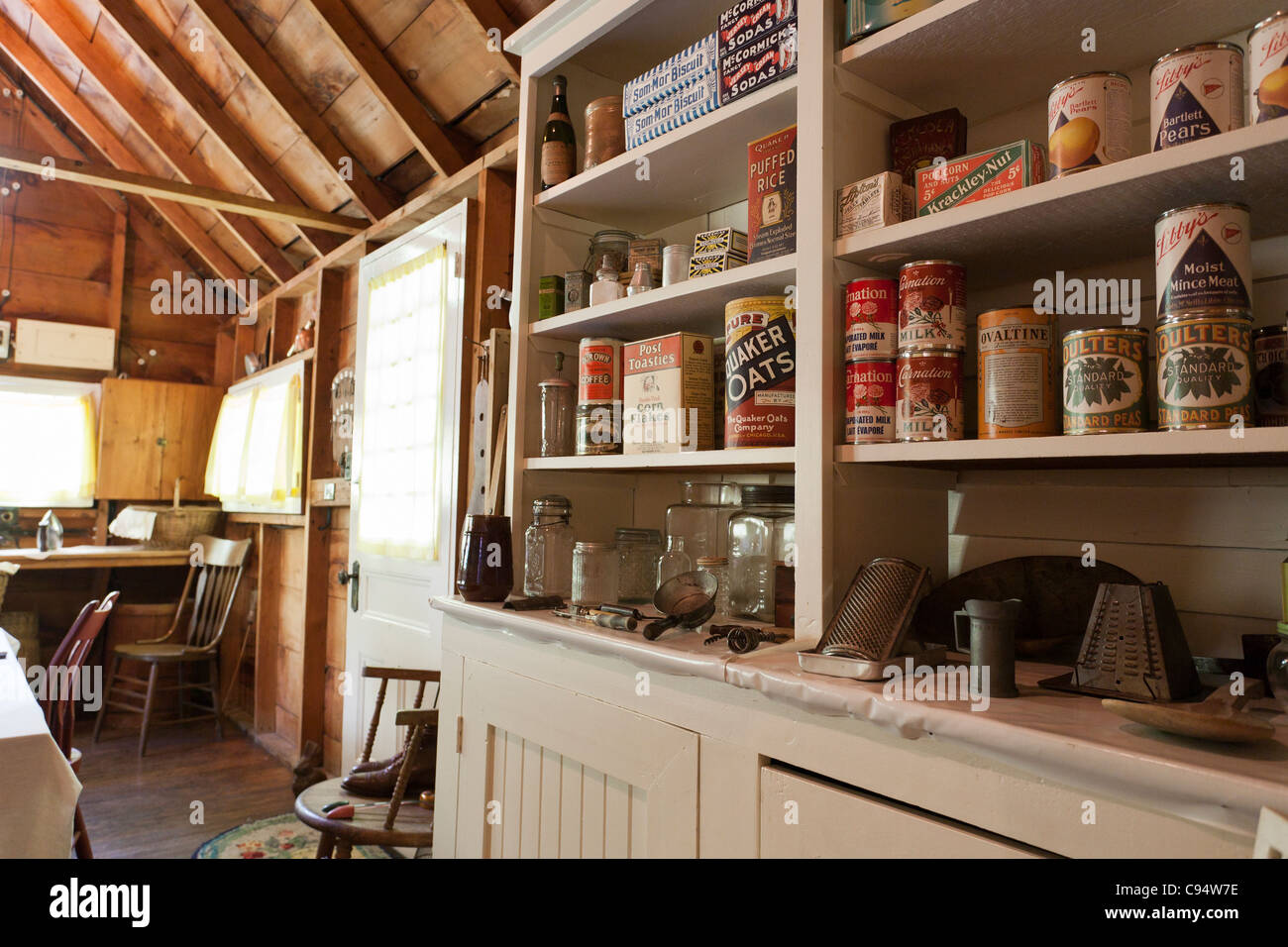 Pre-war Kitchen Shelves at the Estate. A collection of old cans, boxes and kitchen implements fill the kitchen cupboard - Stock Image