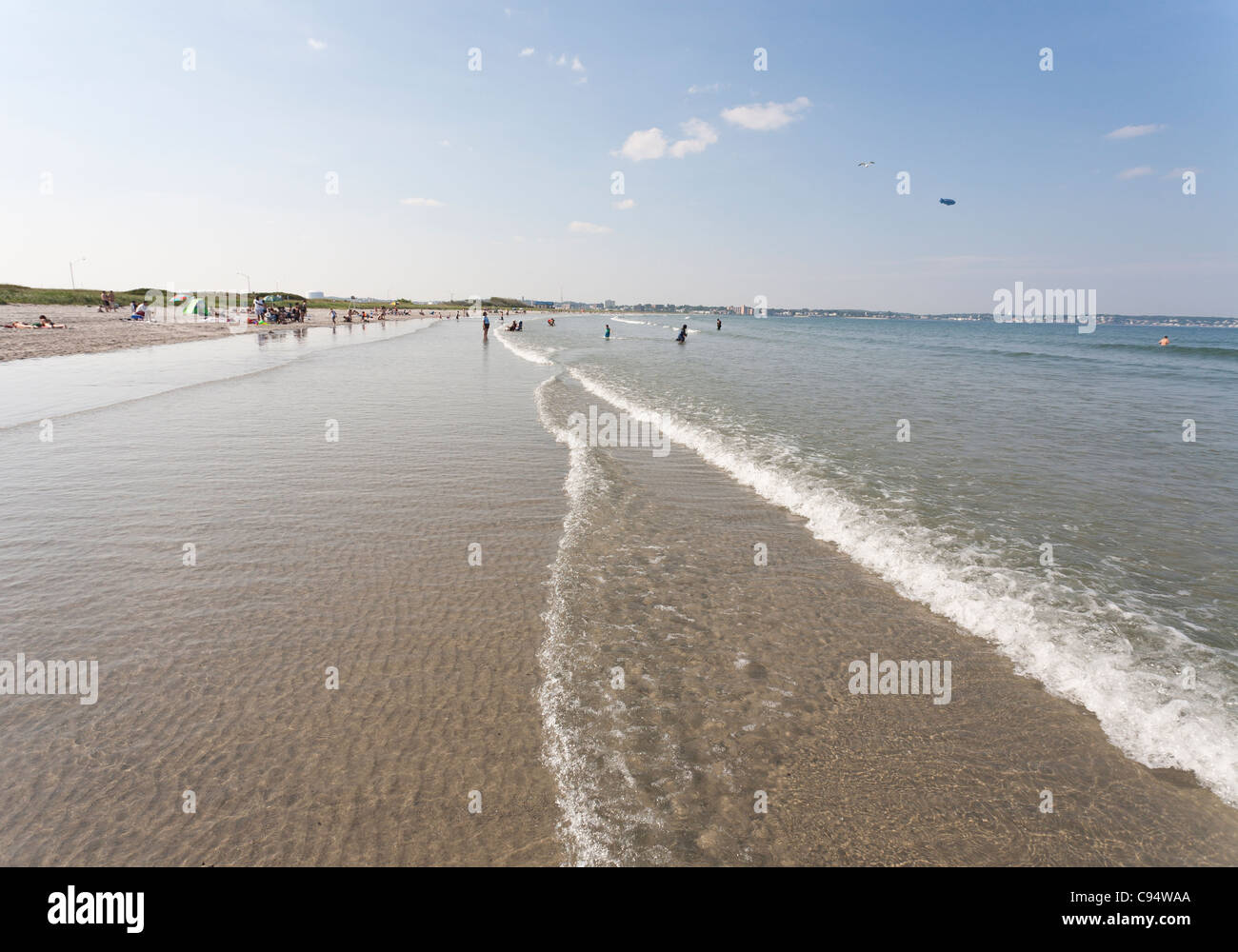 Shallow water waves with blimp and seagull overhead. The view toward Lynn of Long Beach's inviting shallow sandy - Stock Image