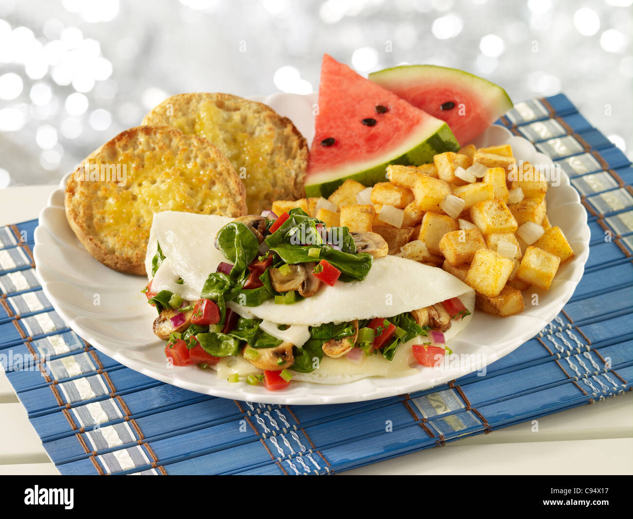 Egg white omelet with spinach, tomato and mushrooms served with potatoes, english muffins and watermelon - Stock Image