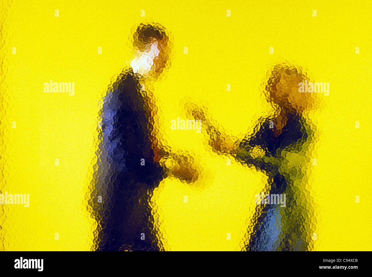 Abstract view of businessman and businesswoman through mottled glass wall - Stock Image