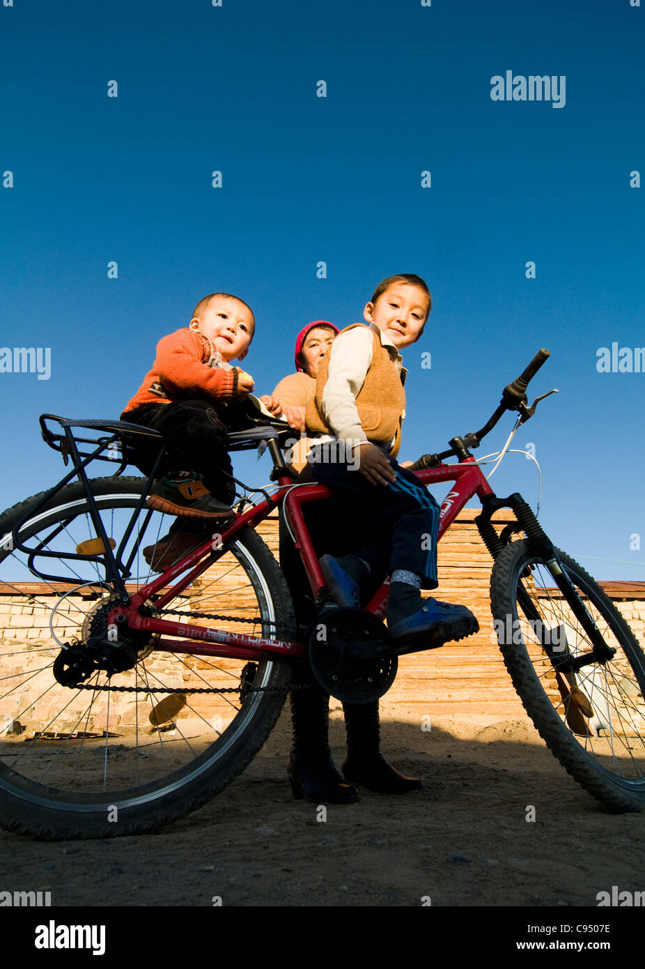 Siblings riding their bicycle with their grandmothers help. Stock Photo