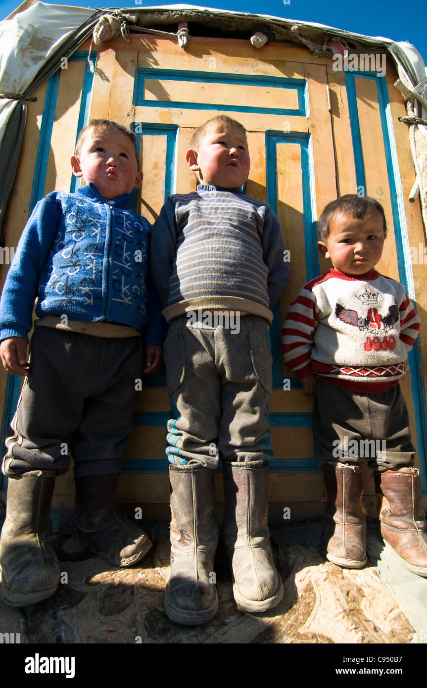 Cute Kazakh children standing by the door to their family yurt. - Stock Image