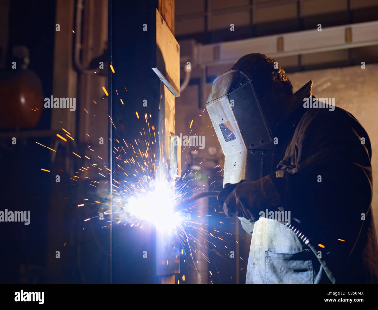 Manual worker in steel factory using welding mask, tools and machinery on metal. Horizontal shape, side view, waist - Stock Image