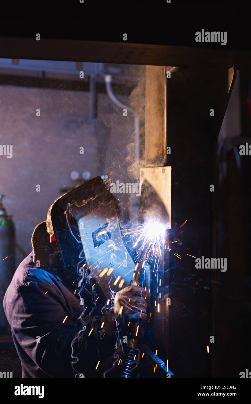 Manual worker in steel factory using welding mask, tools and machinery on metal. Vertical shape, side view, copy - Stock Image