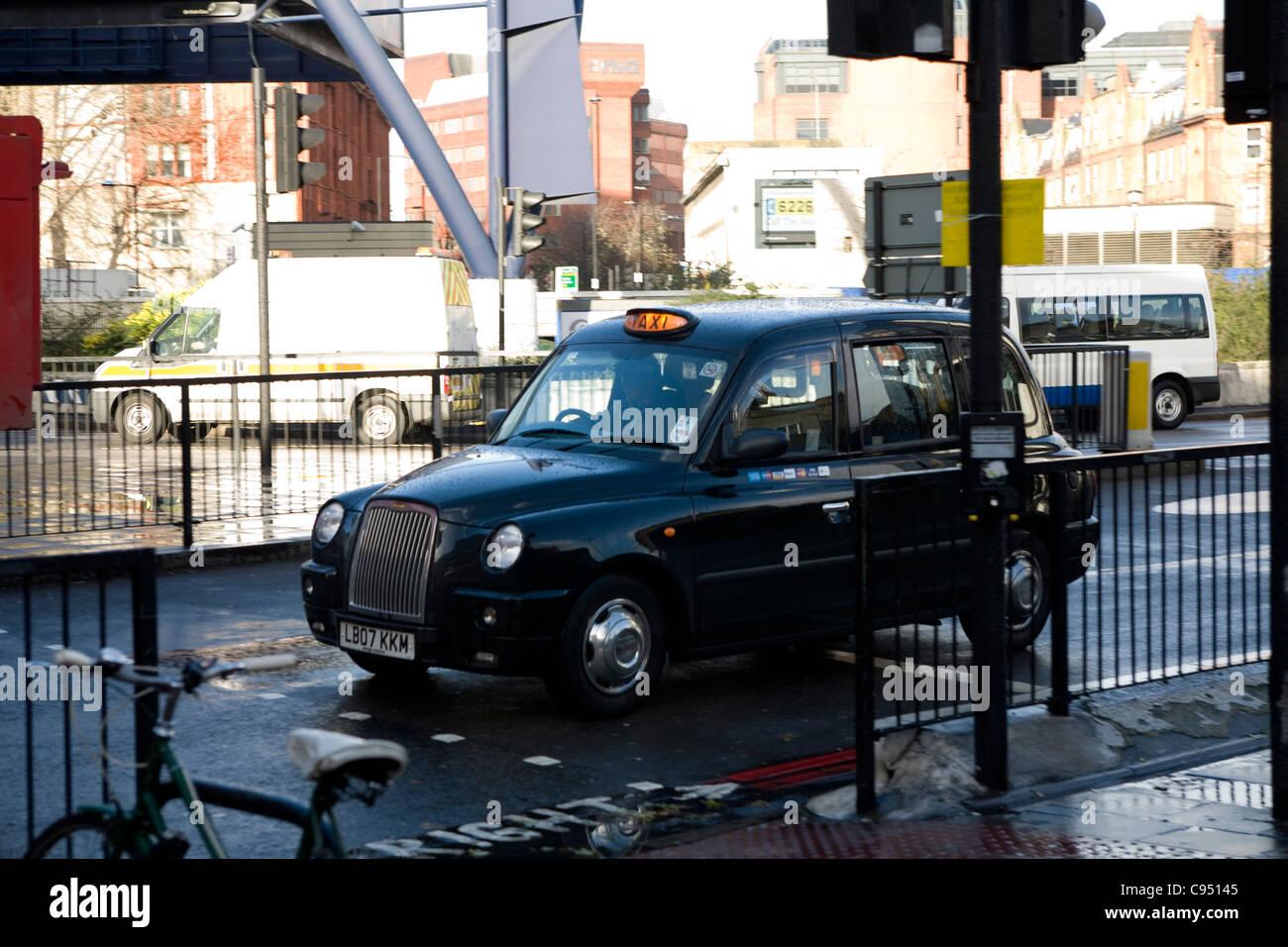 Black cab driving through London street. - Stock Image