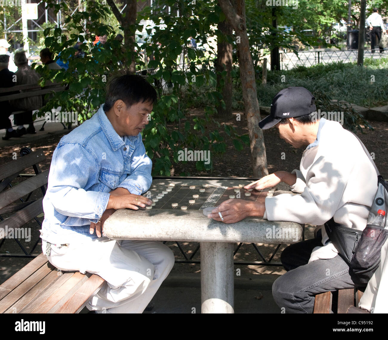 Asian men playing chinese chess in Columbus park in Chinatown, NYC Stock Photo