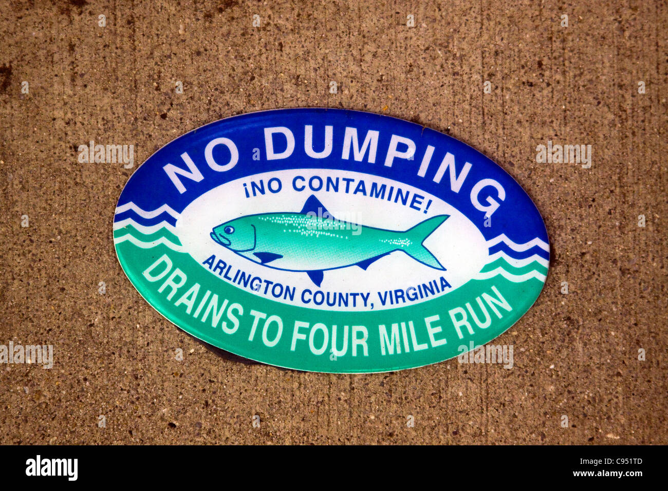 Arlington County and City of Alexandria Virginia No Dumping Drains to Four Mile Run sign on top of a storm water - Stock Image