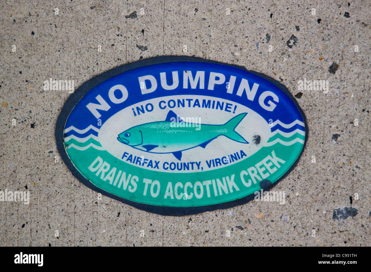 Fairfax County Virginia No Dumping Drains to Accotink Creek sign on top of a storm water drainage catch basin inlet - Stock Image