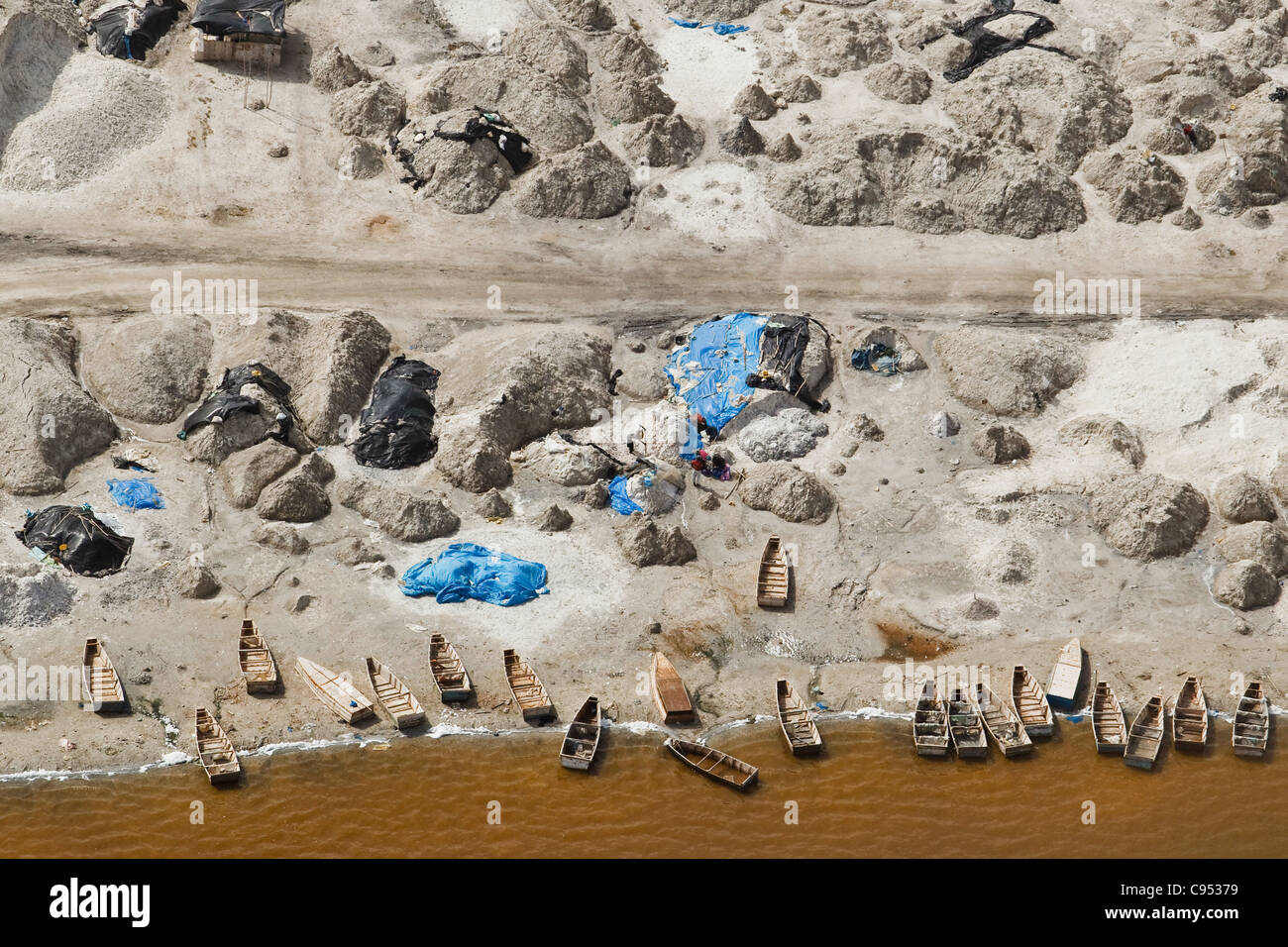 Pirogues and salt production on the shore of Lac Rose (Pink Lake) near Dakar, Senegal. - Stock Image