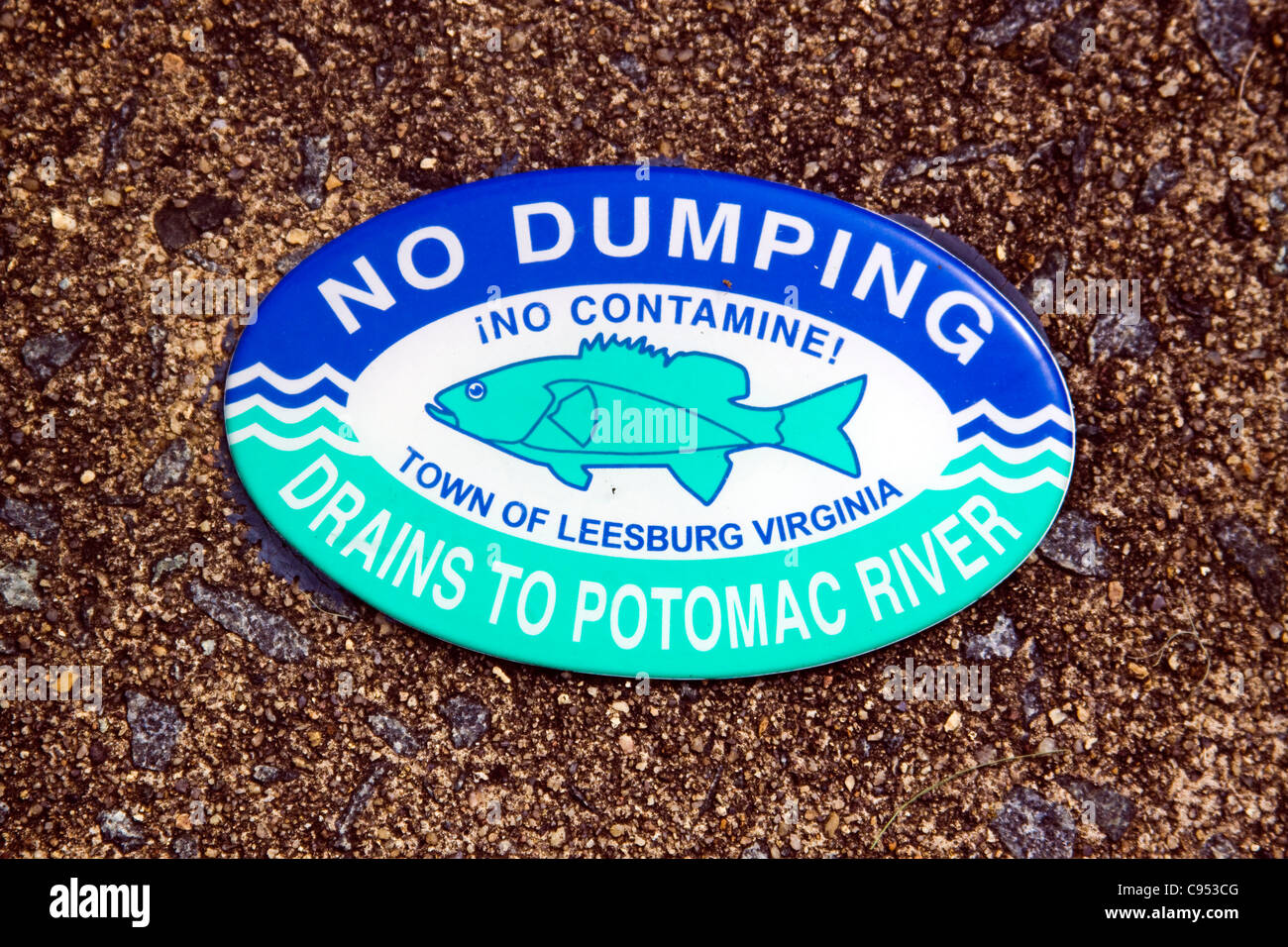 Town of Leesburg Virginia No Dumping Drains to Potomac River sign on top of a storm water drainage catch basin inlet - Stock Image