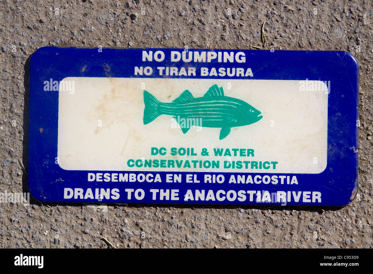 District of Columbia Soil Water Conservation Dist No Dumping Drains to Anacostia River sign on top of a storm drainage - Stock Image
