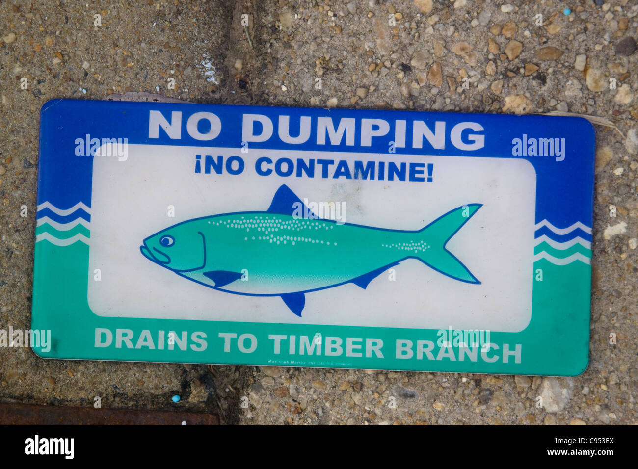 City of Alexandria Virginia No Dumping Drains to Timber Branch sign on top of a storm water drainage catch basin - Stock Image