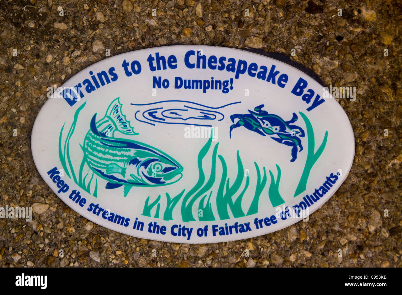 City of Fairfax Virginia No Dumping Drains to the Chesapeake Bay sign on top of a storm drainage structure - Stock Image