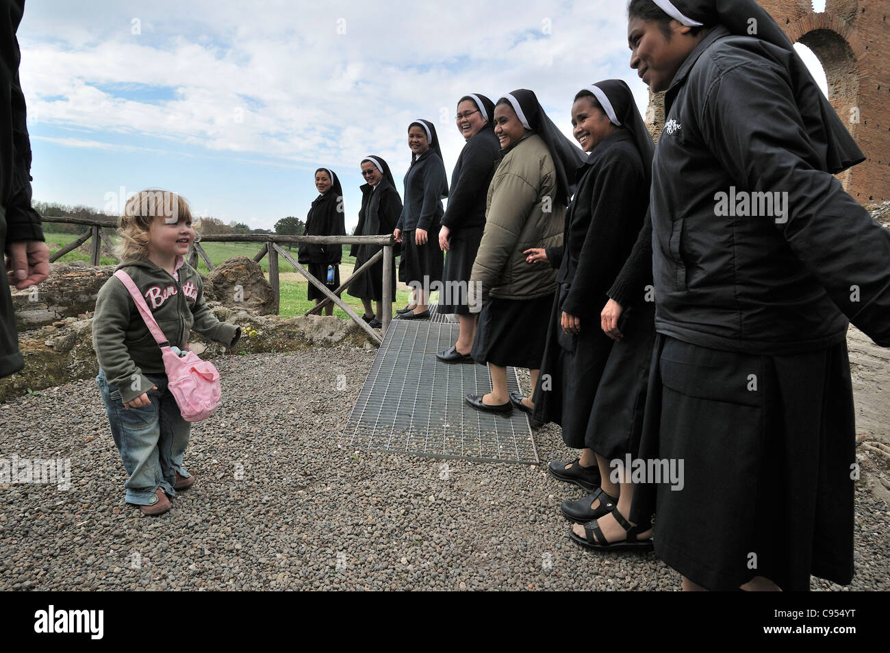 Rome. Italy. Little girl meets a group of nuns at Villa dei Quintili. - Stock Image