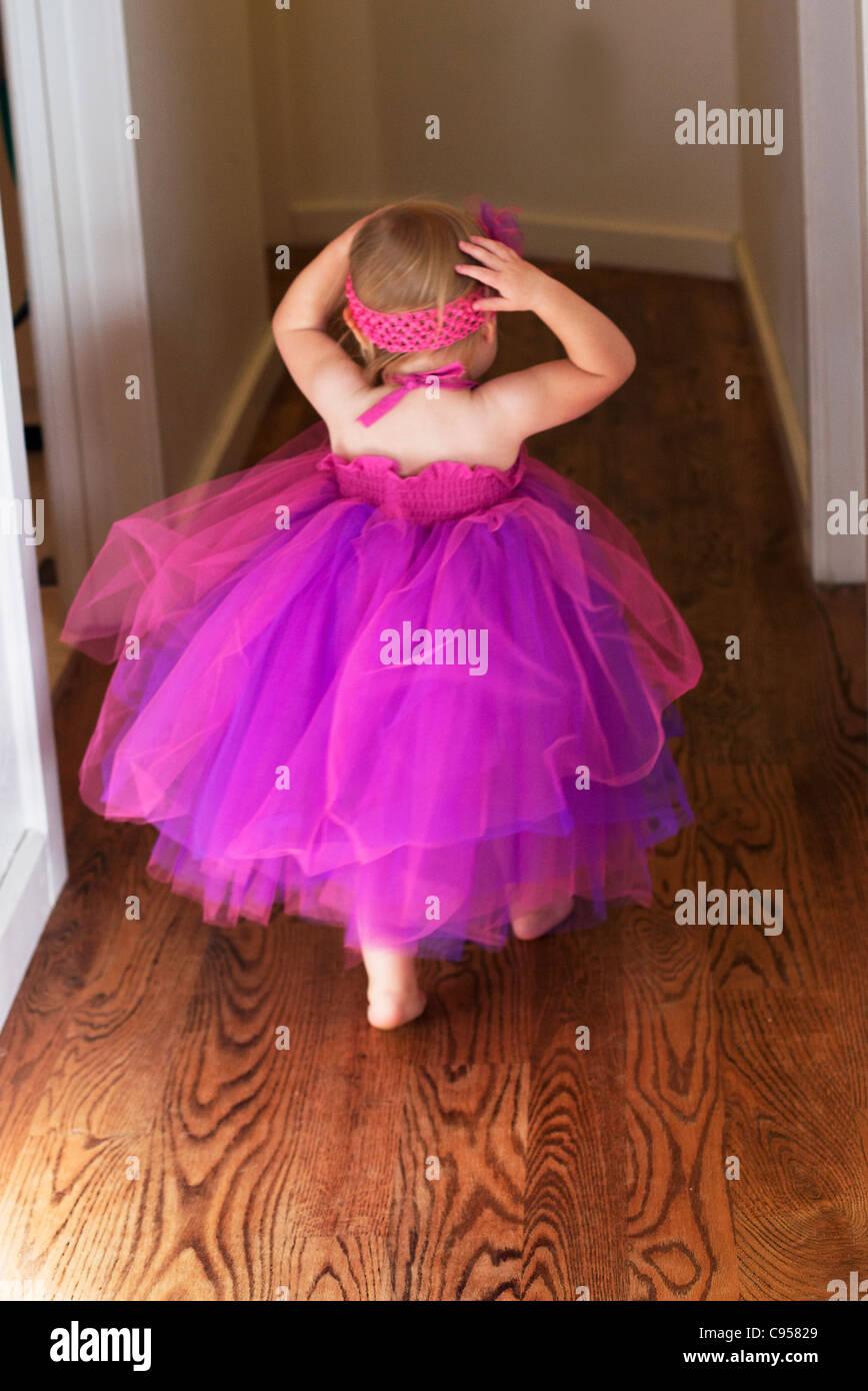 Toddler running down hallway wearing pink dress. - Stock Image