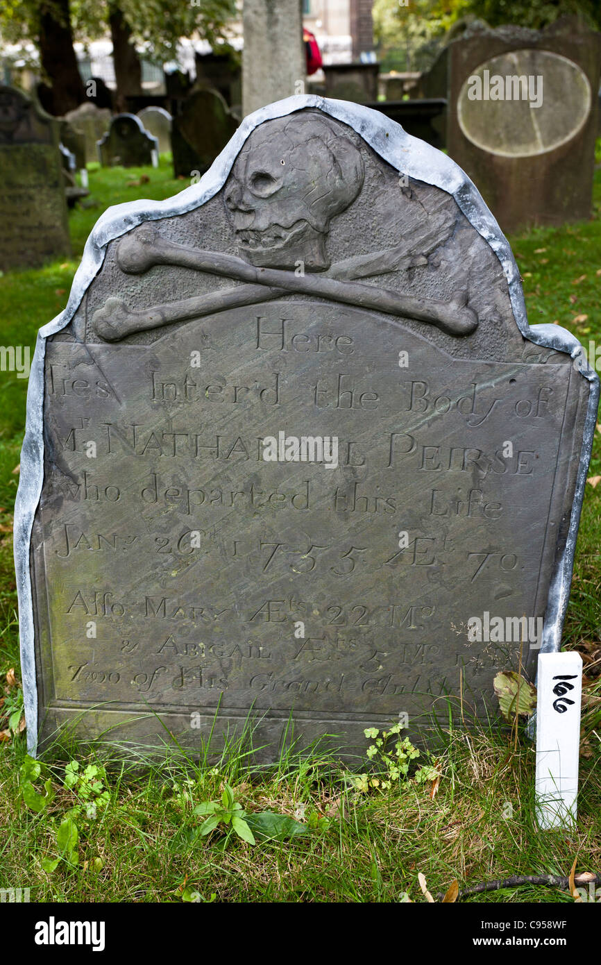 An old Slate Gravestone from 1755. A dark stone fixed with a lead edge and with a skull and cross bones for decoration. - Stock Image
