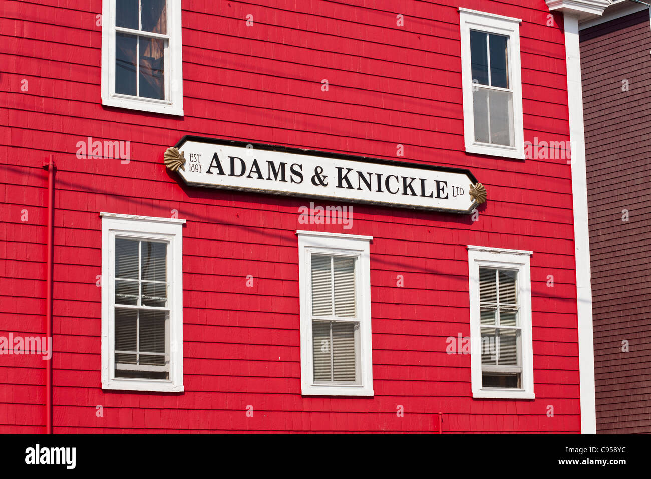 Red Paint White Windows in Lunenburg. The bright red paint on the siding of an old Adams and Knickle building in - Stock Image