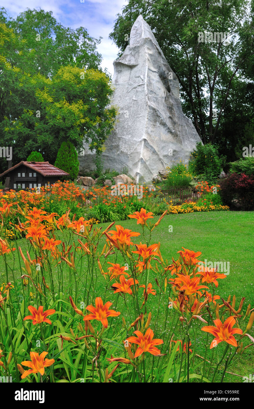 Day lilies frame a representation of the Matterhorn in the Swiss garden at International Peace Gardens in Salt Lake - Stock Image
