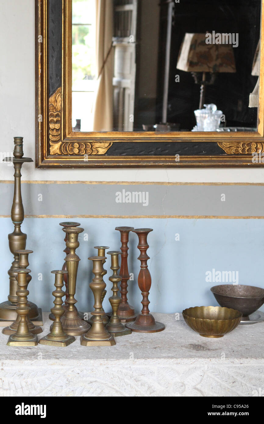 Antique candle holders and bowls on a mantle. - Stock Image