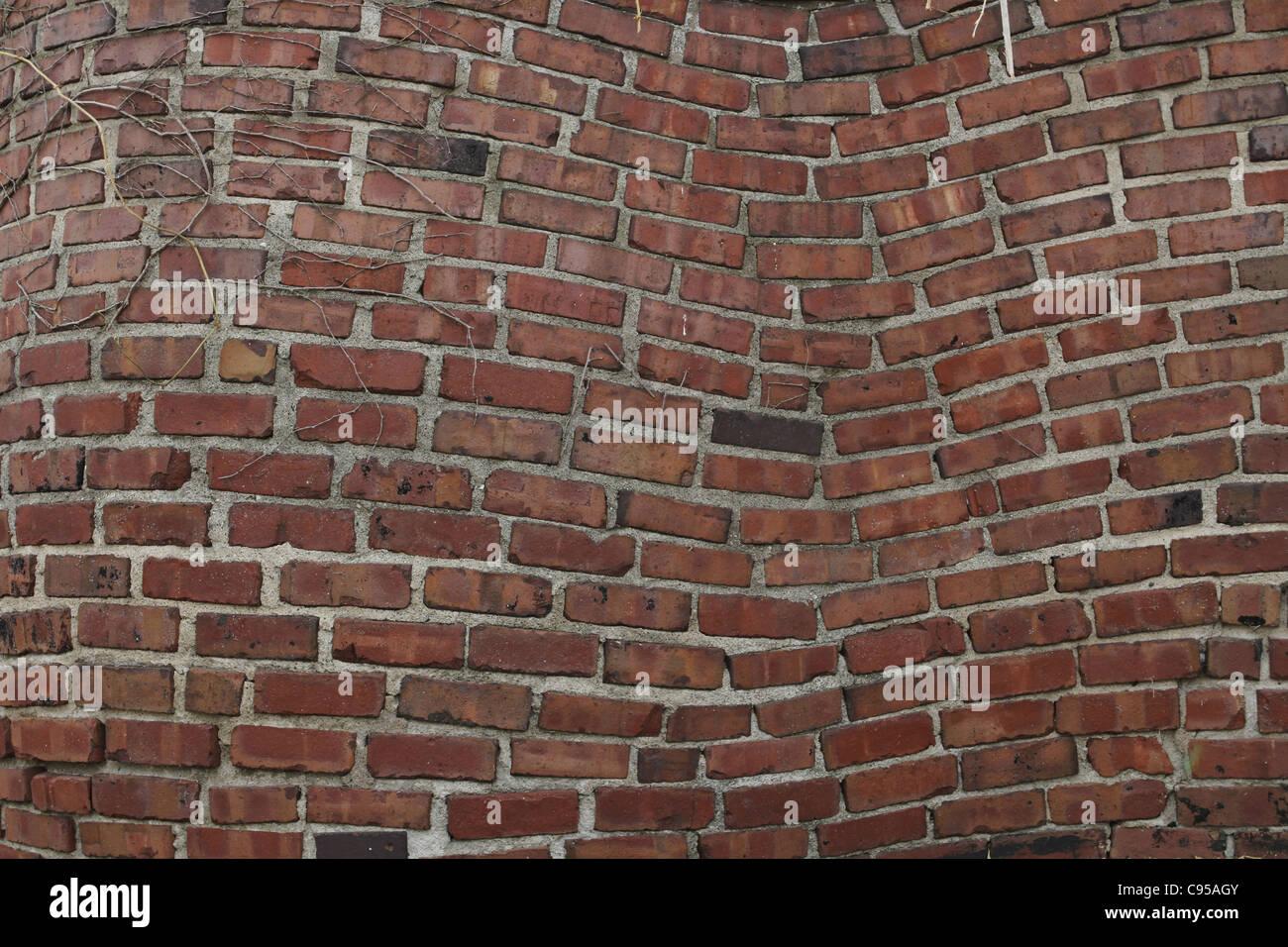 A warped looking brick wall. - Stock Image