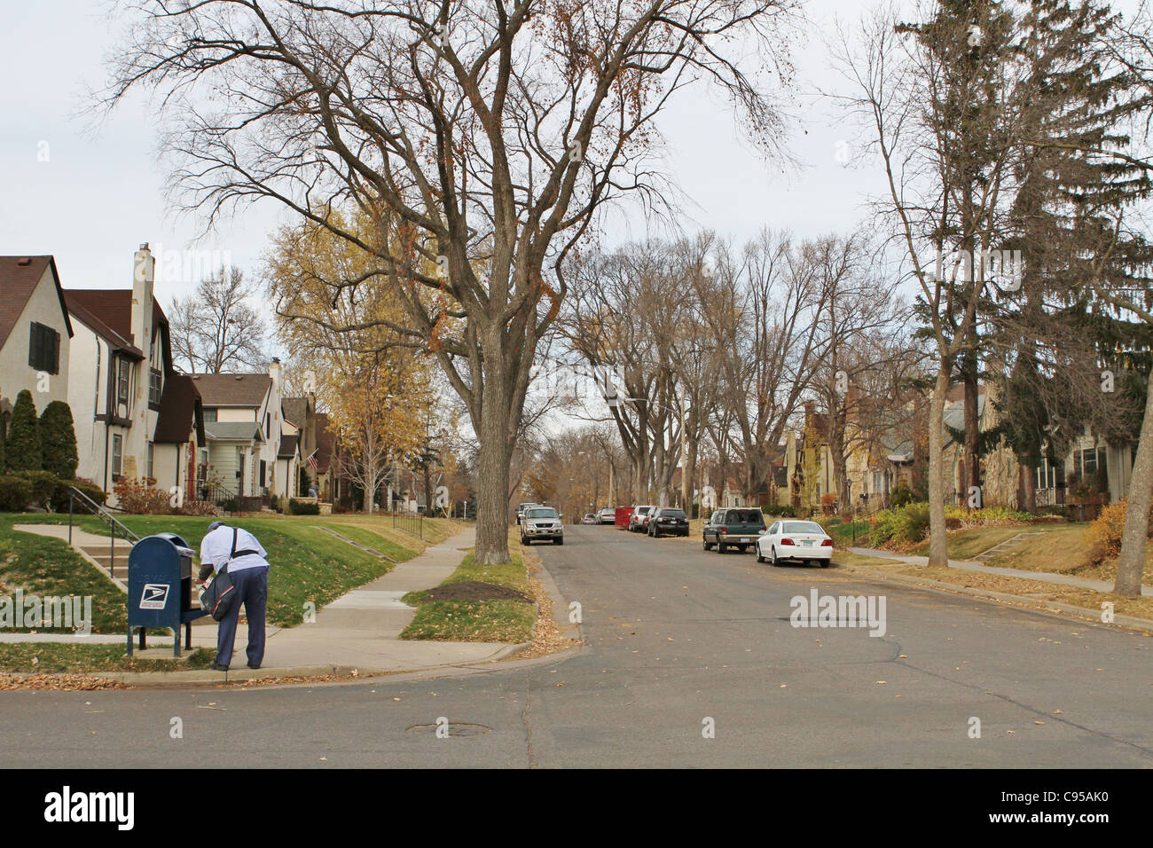 A mailman picks up mail at a box on a street corner in Minneapolis, MInnesota - Stock Image