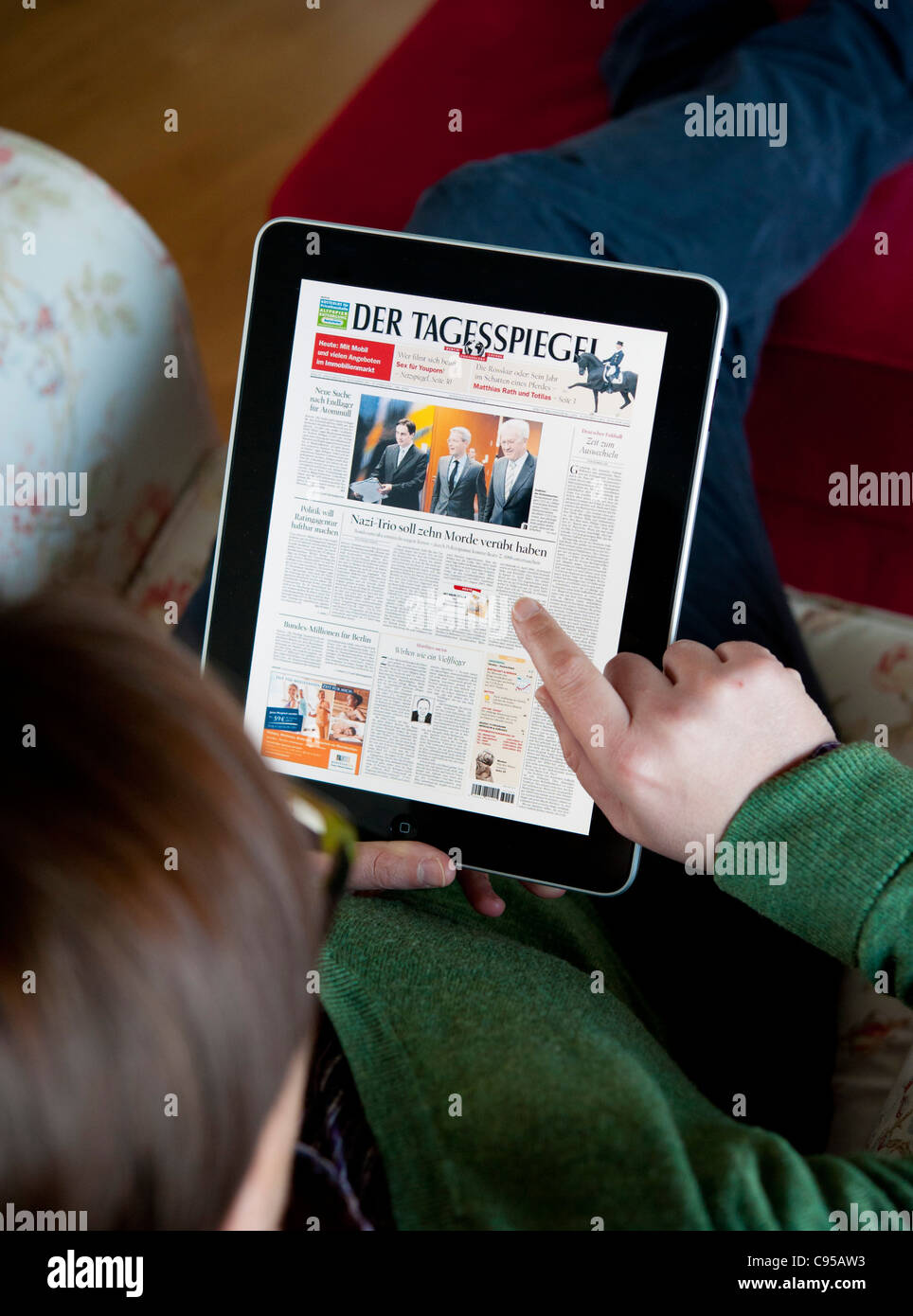 Woman using iPad tablet computer to read digital edition of Der Tagesspiegel newspaper in Germany - Stock Image