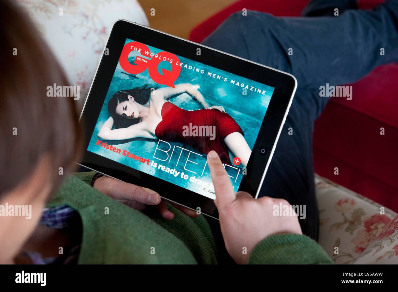 Woman using iPad tablet computer to read GQ magazine online edition - Stock Image