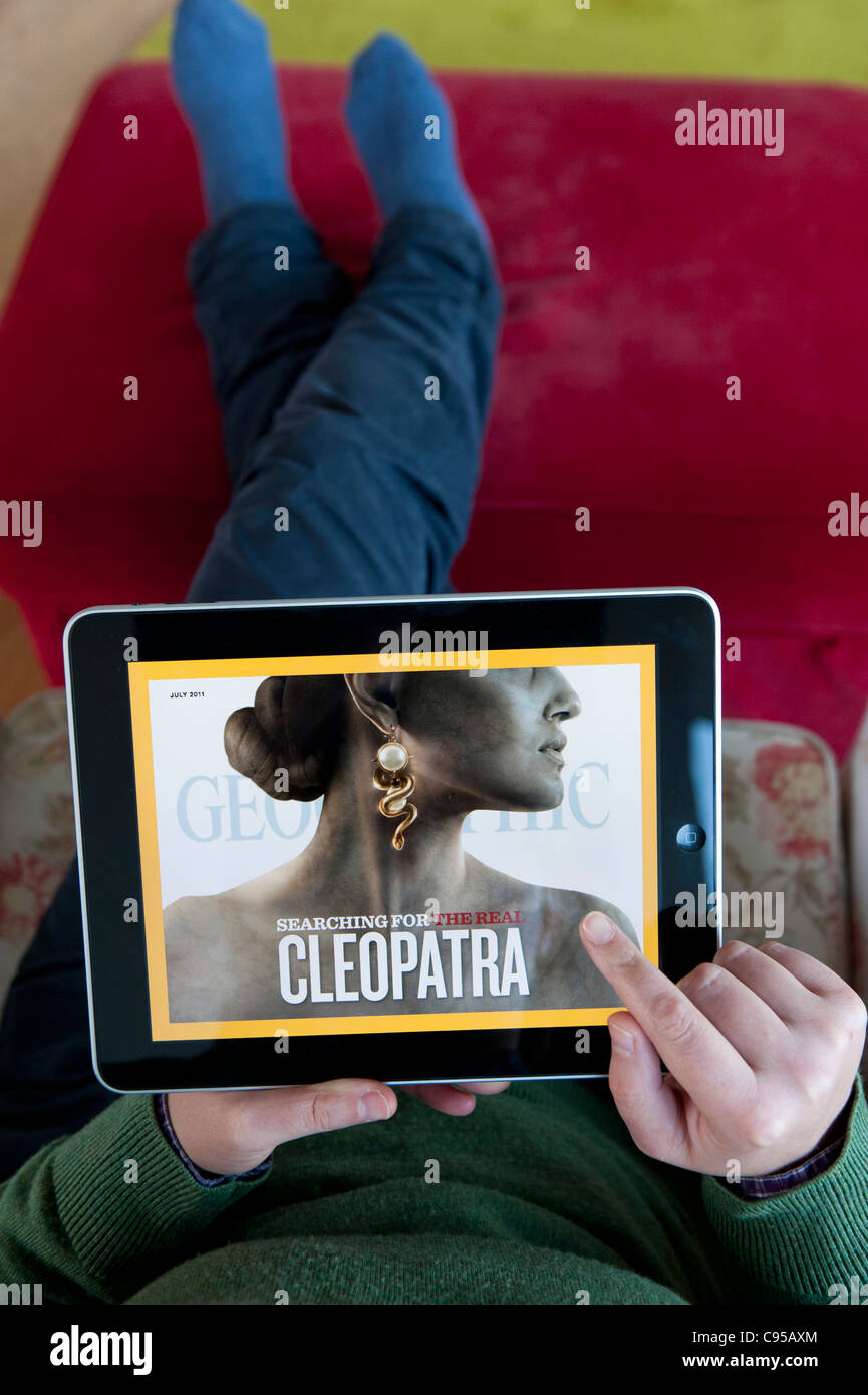 Woman using iPad tablet computer to read National Geographic magazine online edition - Stock Image