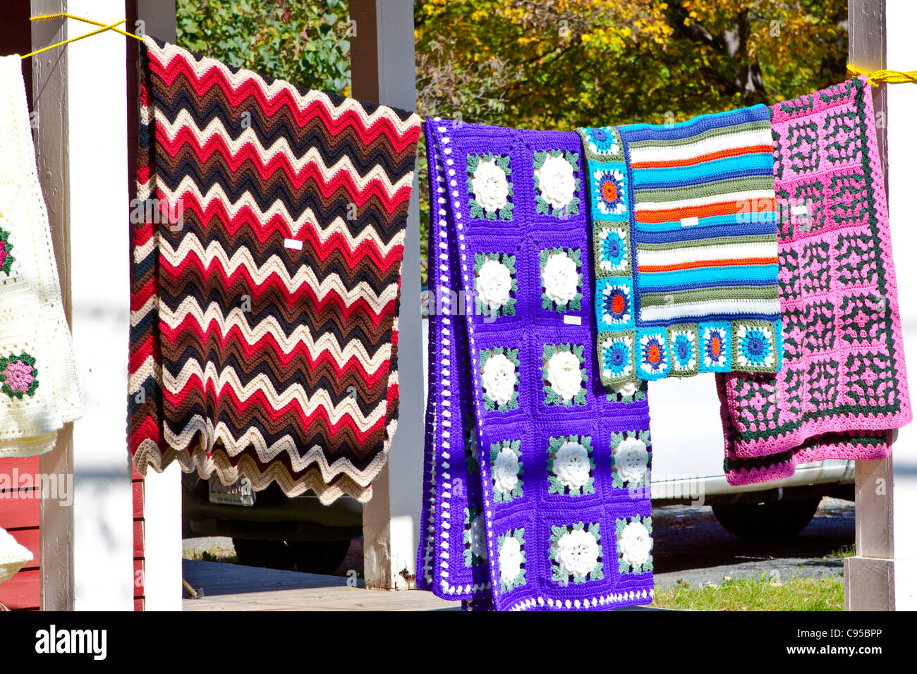 Colorful quilts hang on a porch - Stock Image