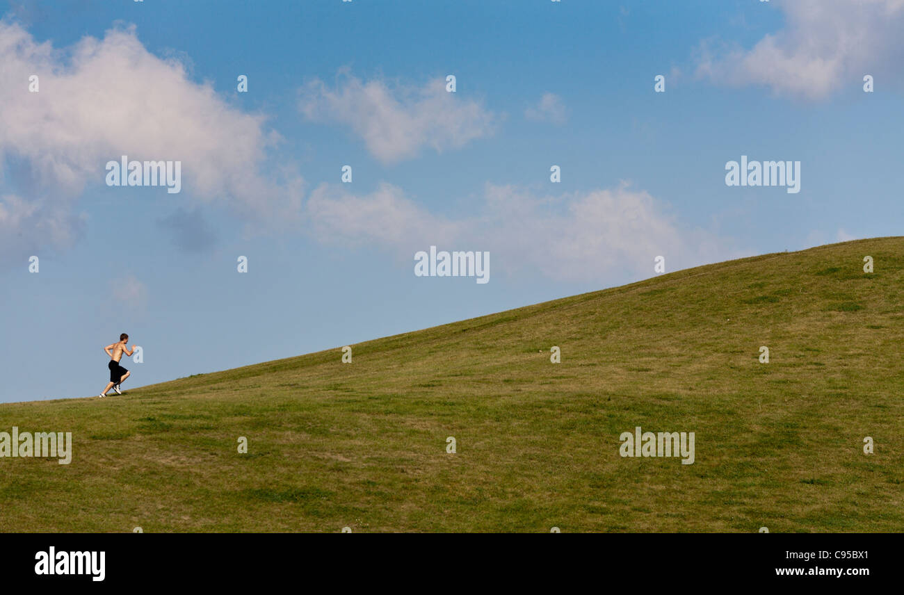 Training Uphill. A lone male runner sprints up a grassy hill in an Ottawa park. - Stock Image