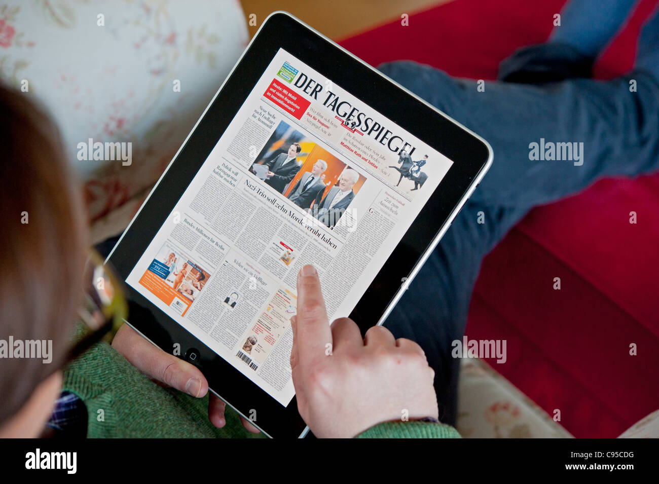 Woman using iPad tablet computer to read Der Tagesspiegel German Berlin daily newspaper online - Stock Image