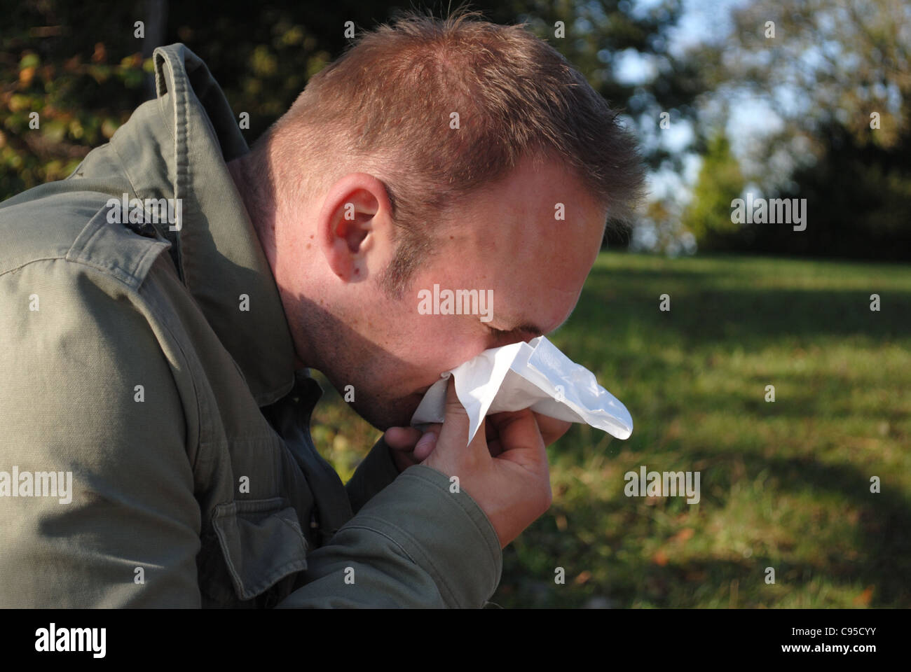 man blowing his nose (cold,flu,allergy) - Stock Image