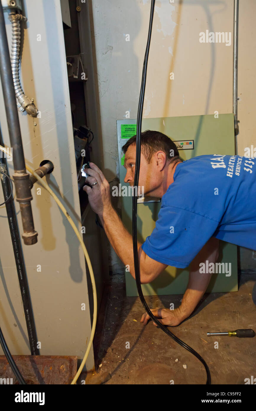 Technician Repairs Natural Gas-Fired Forced-Air Furnace - Stock Image