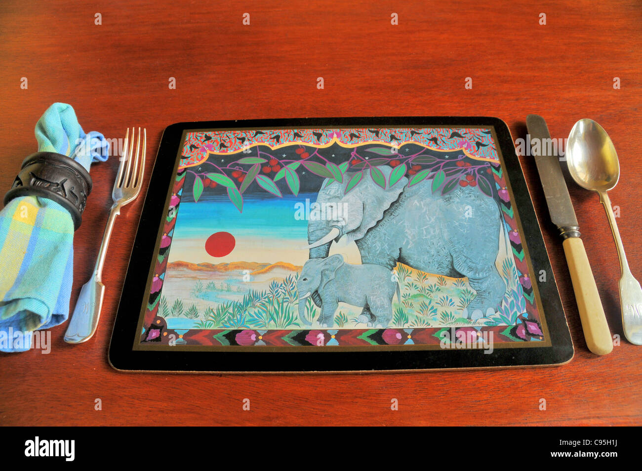 Asian elephant design place mat with with knife and fork and napkin set out on a wooden dining table. - Stock Image