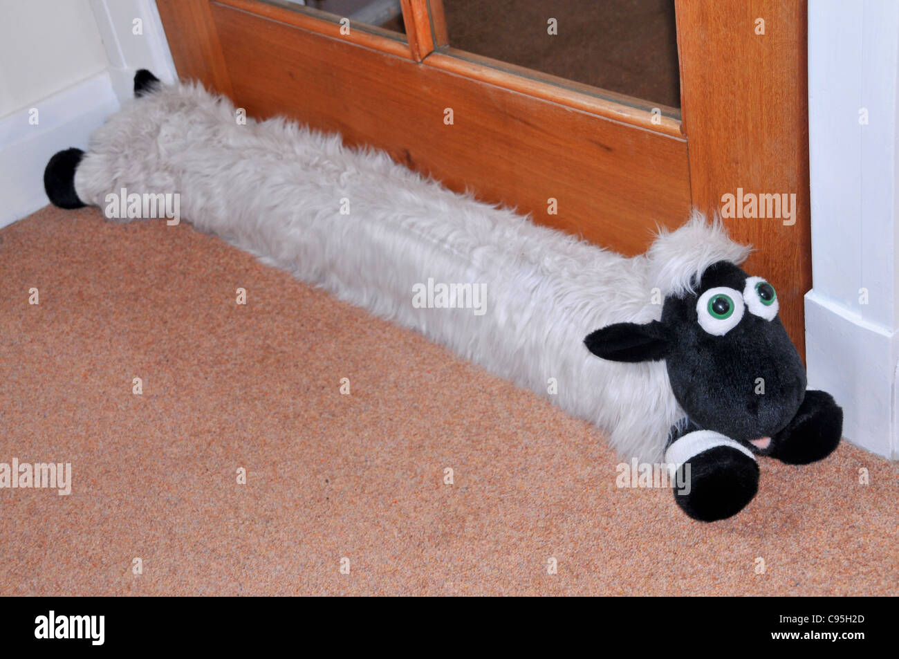 A door draft excluder in the shape of a sheep. - Stock Image