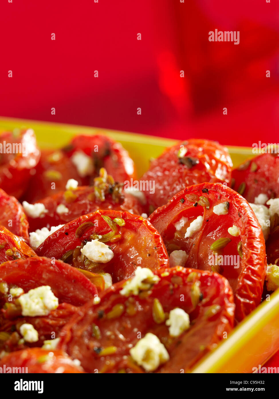 Roasted tomatoes with crumbled cheese in a casserole dish - Stock Image