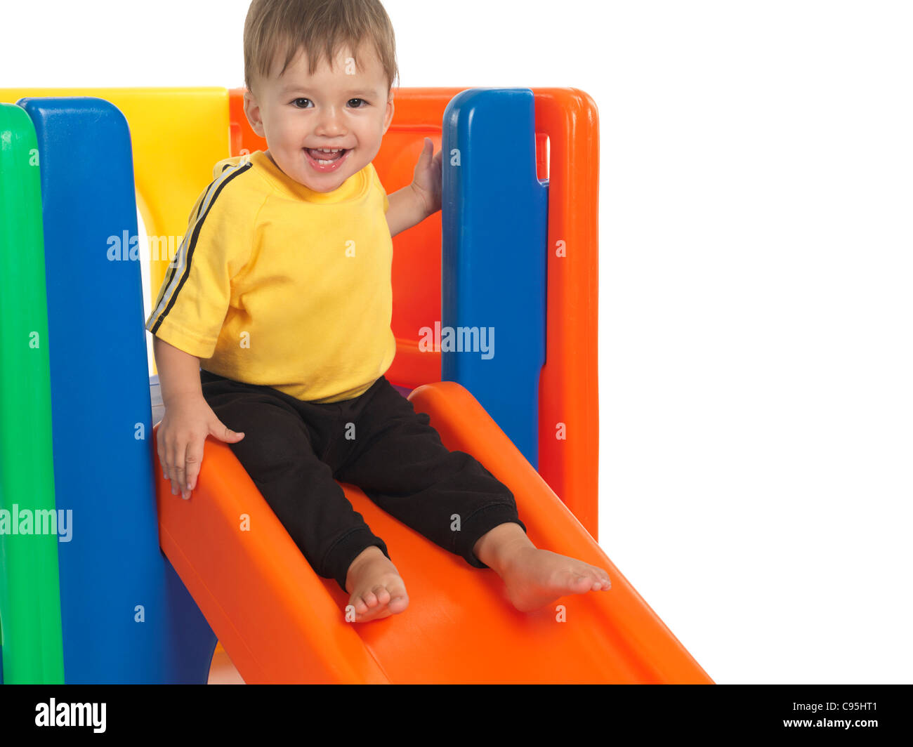Happy one and a half year old child on a slide. Isolated on white background. - Stock Image