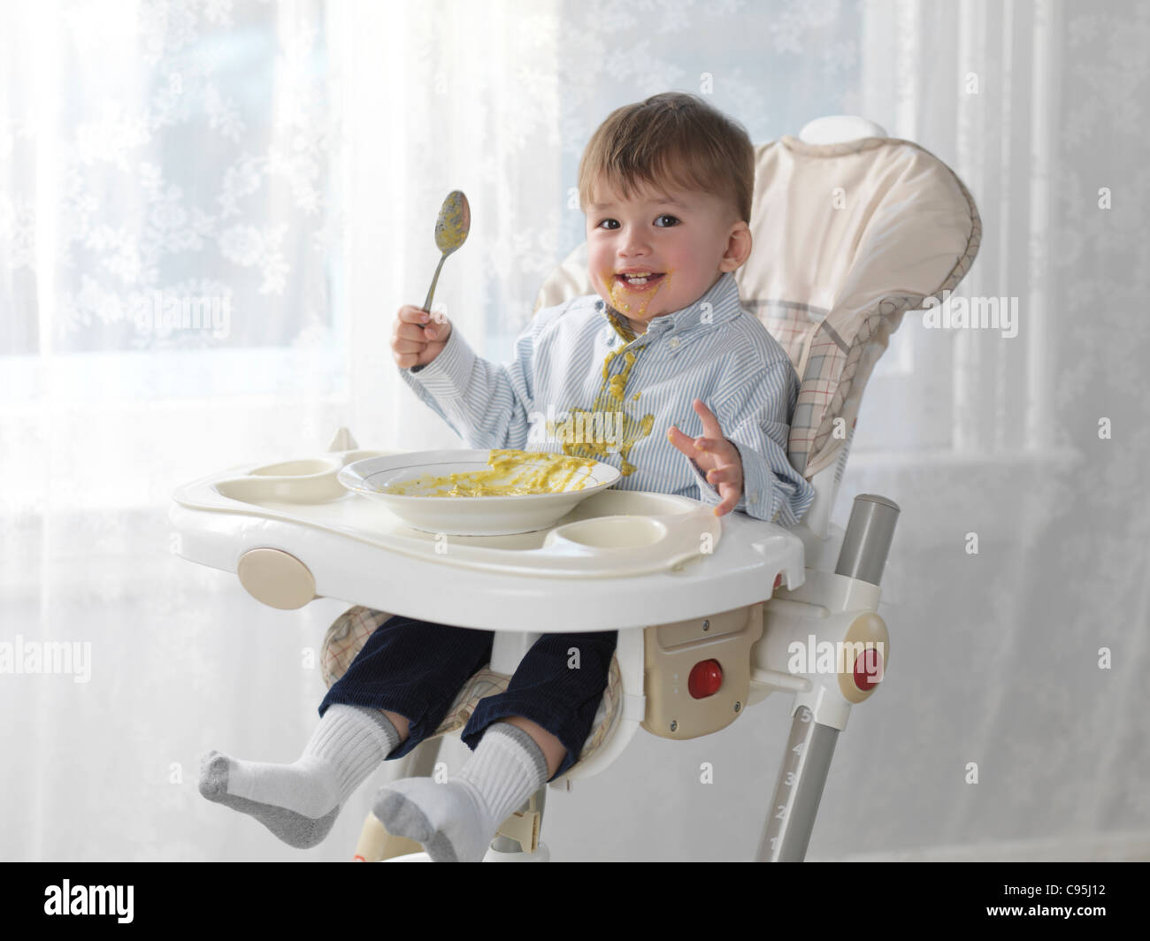 One and a half year old happy boy sitting in a high chair and eating soup with a spoon, spilling it on his shirt - Stock Image