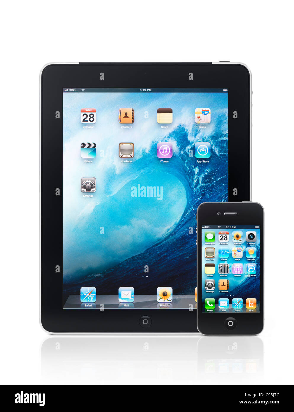 Apple iPad 3G tablet computer and iPhone 4 smartphone with desktop icons on their displays isolated on white background - Stock Image
