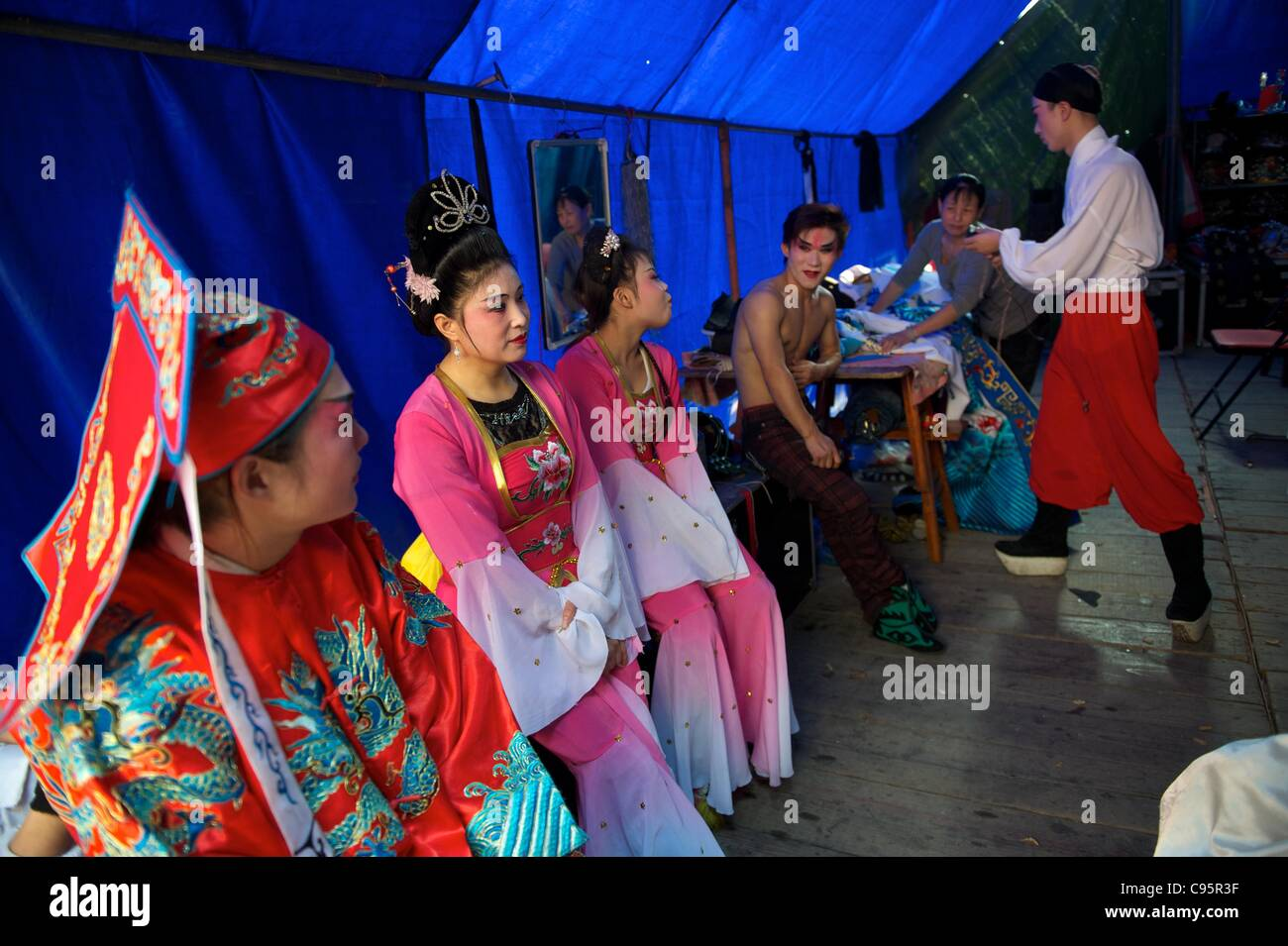 Chinese Huangmei opera artists from Anhei province rest backstage during a commercial performance for villagers - Stock Image