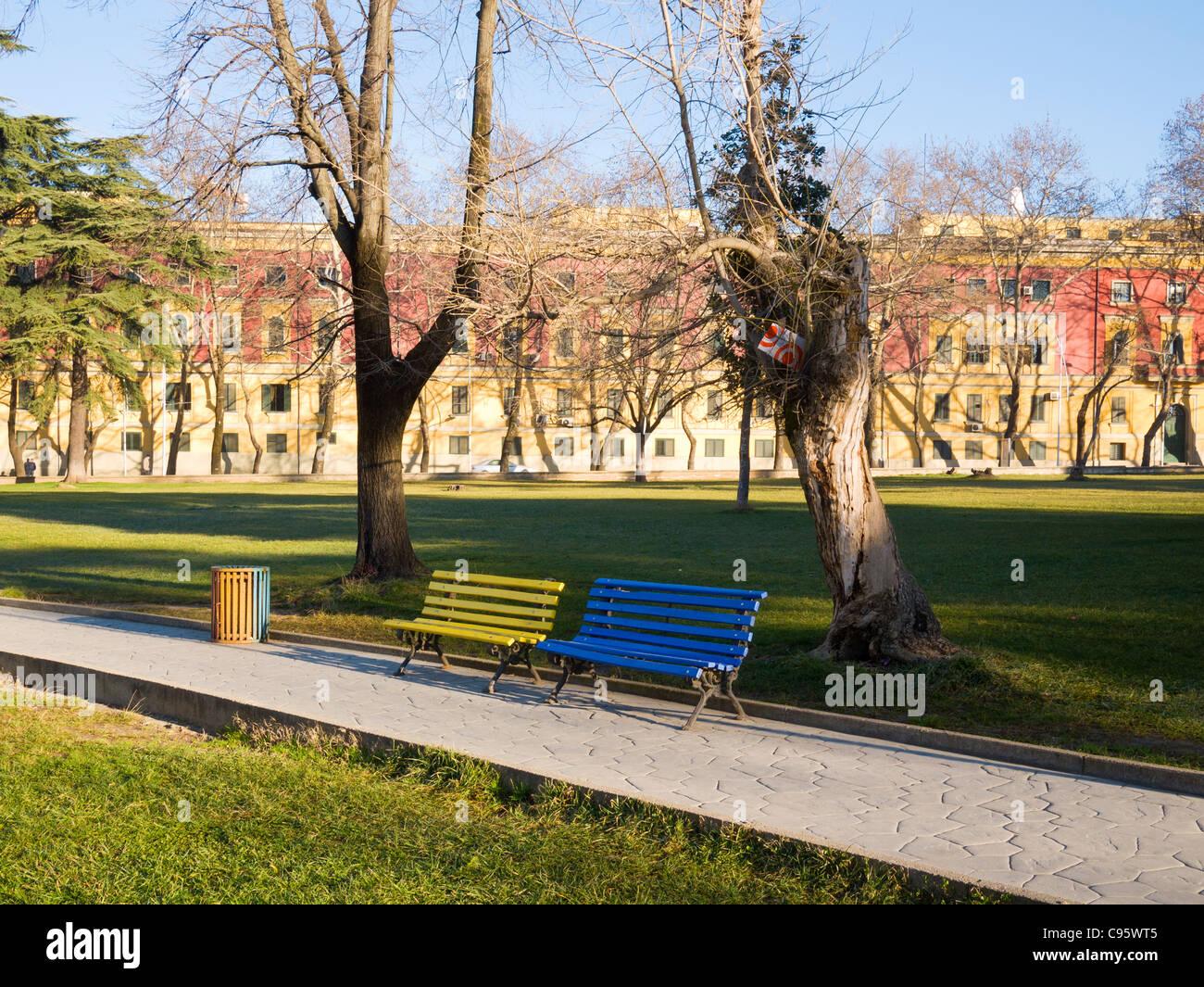 Multi-coloured benches and rubbish bin in Parku Rinia, Tirana, Albania. - Stock Image