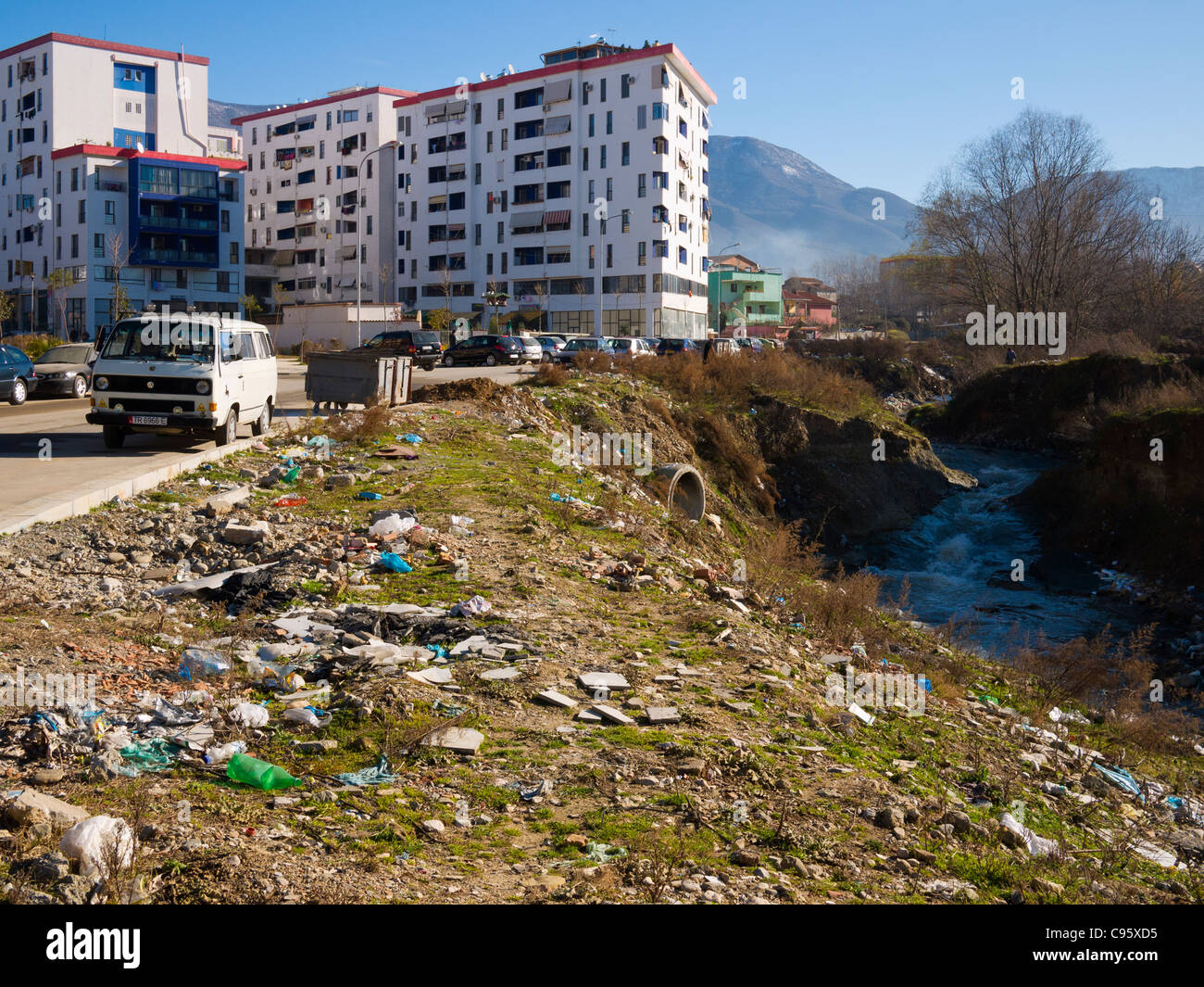 Litter on the banks of the River Lana, Bulevardi Zhan D'Ark, Tirana, Albania.  Modern apartment blocks are nearby. - Stock Image