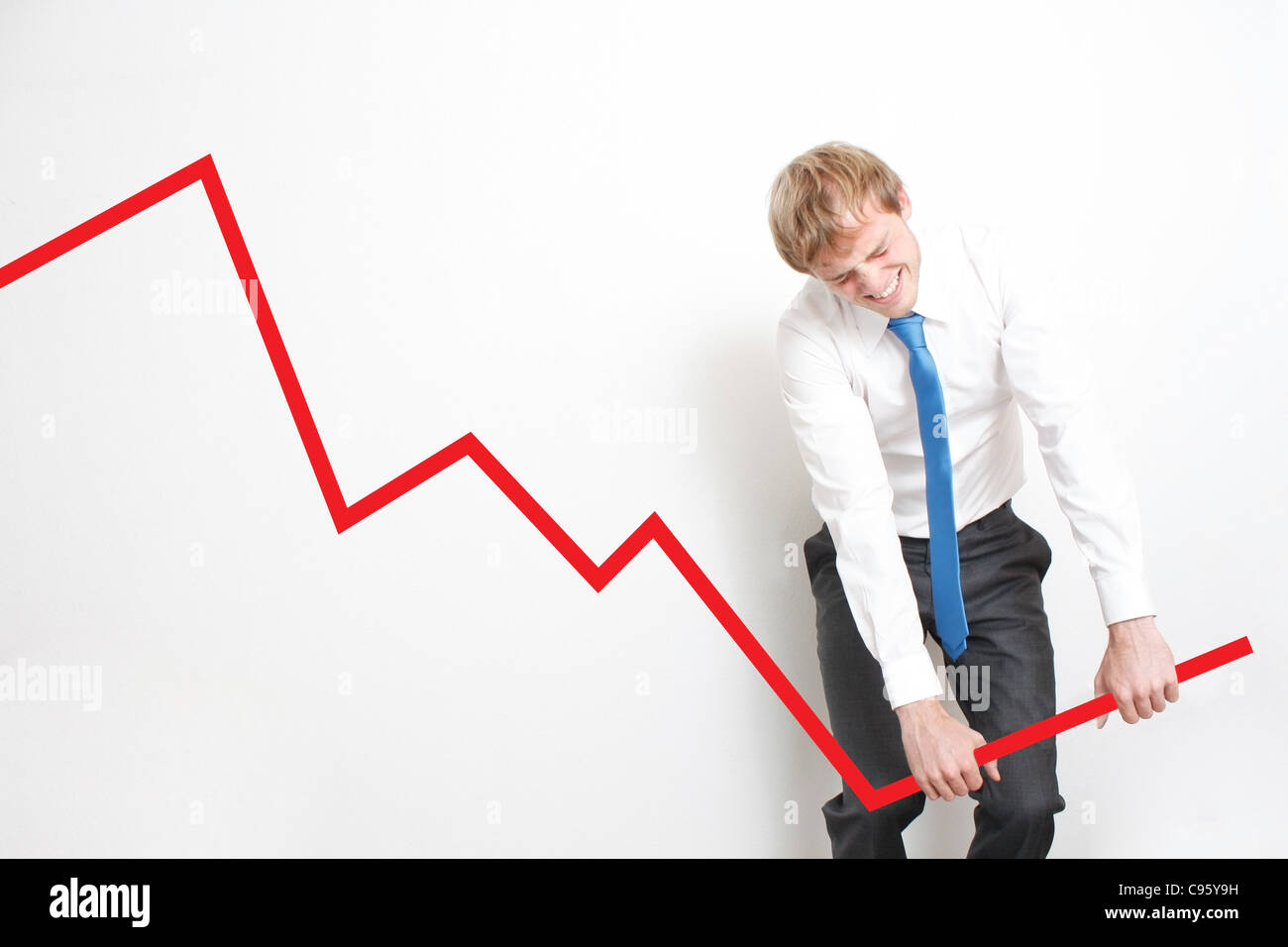 Business man trying to save the downturn - Stock Image