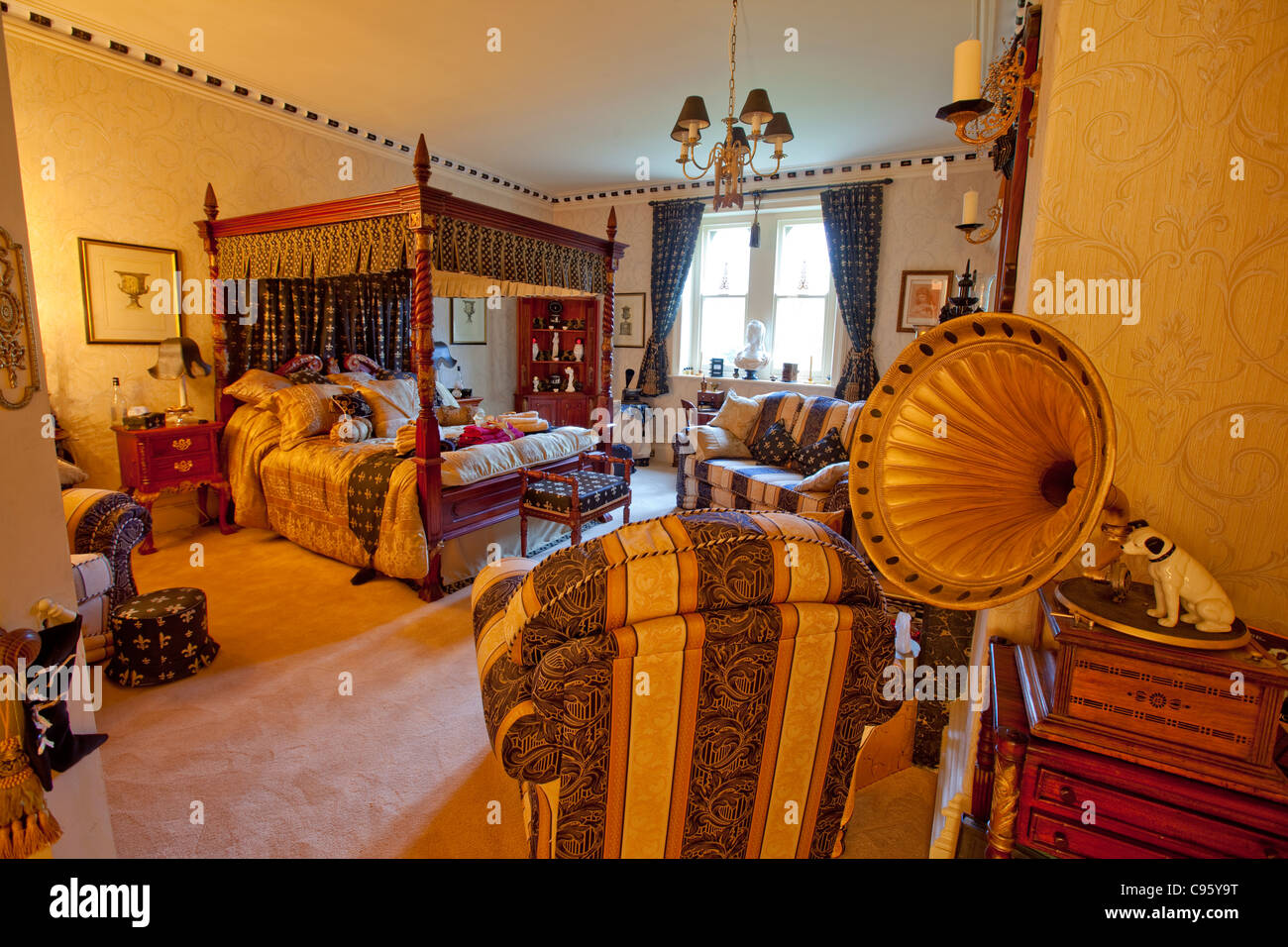 A plush bedroom complete with a four poster bed at Abbey Cwm Hir stately home. - Stock Image