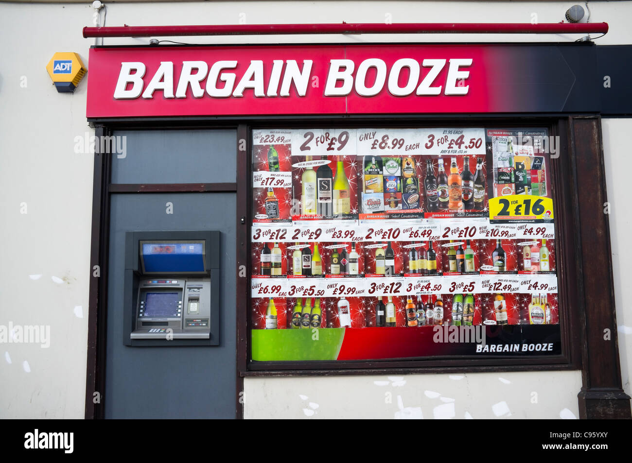 Bargain Booze Shop - with a display window of adverts and very tempting special offers -  there is also a handy - Stock Image