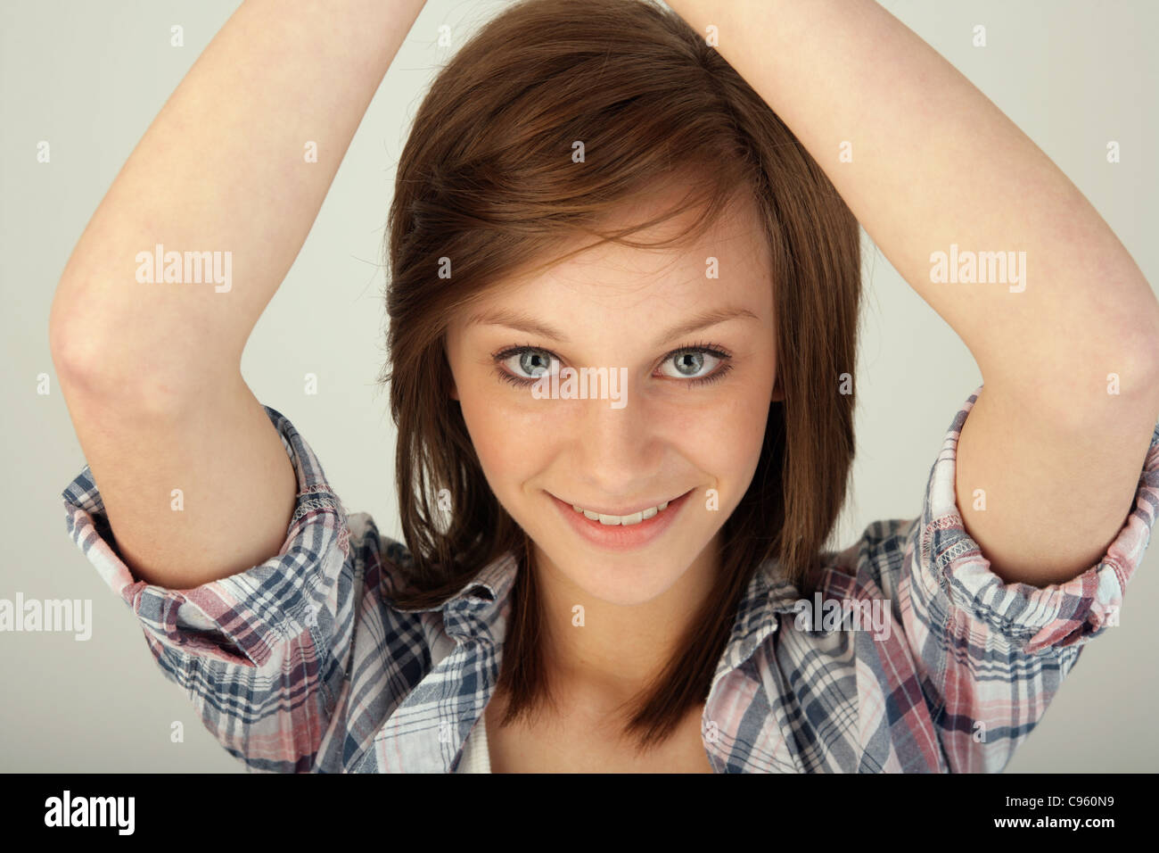 Teenage girl with her arms raised above her head. Stock Photo